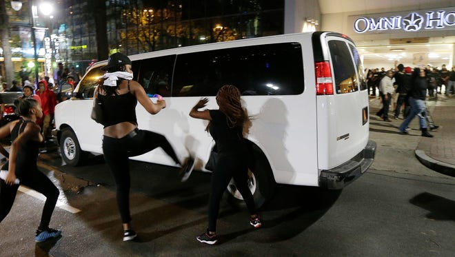 Demonstrators protest Tuesday's fatal police shooting of Keith Lamont Scott in Charlotte Wednesday. Protesters rushed police in riot gear at a downtown Charlotte hotel and officers have fired tear gas to disperse the crowd. At least one person was injured in the confrontation, though it wasn't immediately clear how. Firefighters rushed in to pull the man to a waiting ambulance.