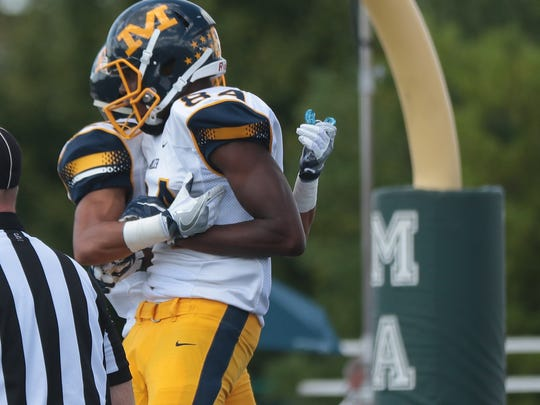 Moeller's Eric Wills celebrates after scoring a touchdown during the Crusaders' football game against Mason, Sunday, Sept. 11, 2016.