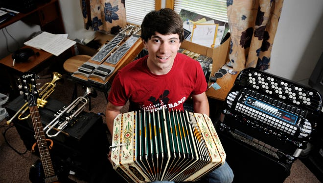 Nathan Neuman, 20, of Nathan's Oldtime Band with some of the instruments he plays Wednesday at his home in Waite Park.