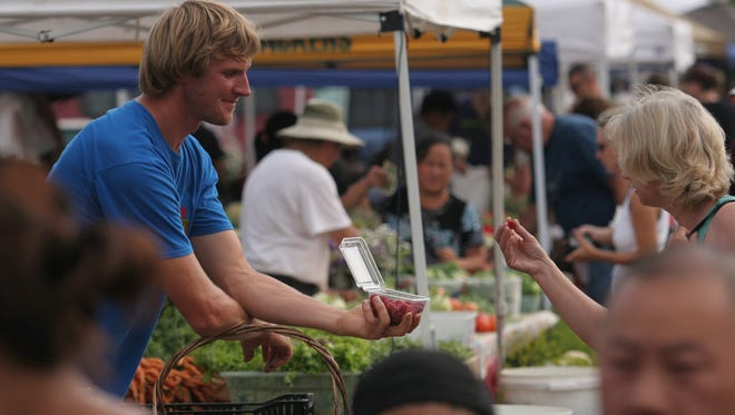 Tony Schultz of Stoney Acres Farm offers a woman a raspberry in July 2011 at the Farmers Market in Wausau. Daily Herald Media file photo Tony Schultz of Stoney Acres Farm offes a woman a raspberry, Saturday, July 23, 2011, at the Farmers' Market in Wausau.