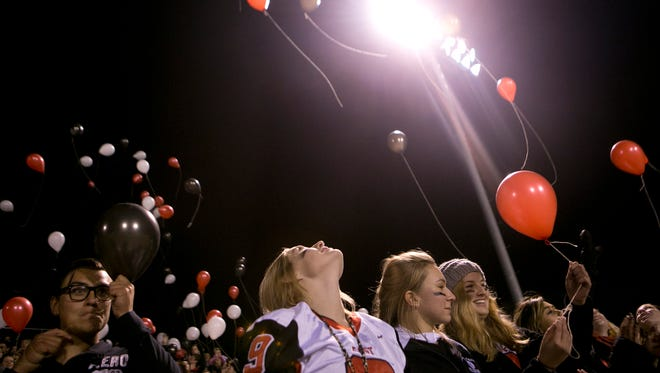 The Wausau East student section releases balloons in honor of Paige Bootz at half time of the Log Game at Thom FIeld in Wausau, Friday, Oct. 2, 2015.