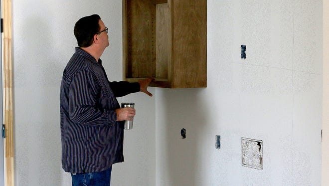 Brad Love looks at built-in cabinets in a home being built on Pennsylvania Road for Maxine after he and several other officers saw a need in the community they serve.