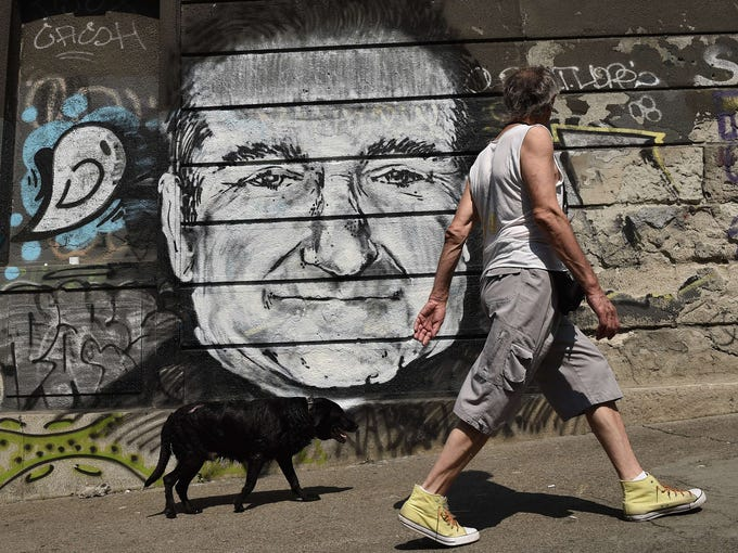 A man walks his dog past a mural depicting actor Robin Williams in downtown Belgrade, Serbia on Aug. 13.Williams died Aug. 11 in an apparent suicide. He was 63.