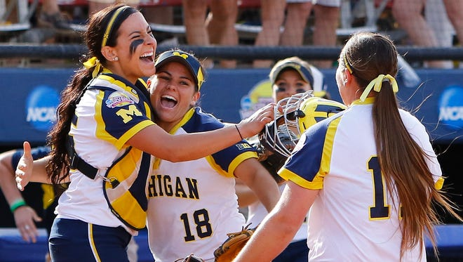 Michigan catcher Lauren Sweet, left, third baseman Lindsay Montemarano, center, and pitcher Kelsey Selman, right, celebrate after Michigan defeated LSU during an NCAA Women's College World Series game in Oklahoma City, Sunday, May 31, 2015. Michigan won 6-3 and moves on to the championship series.