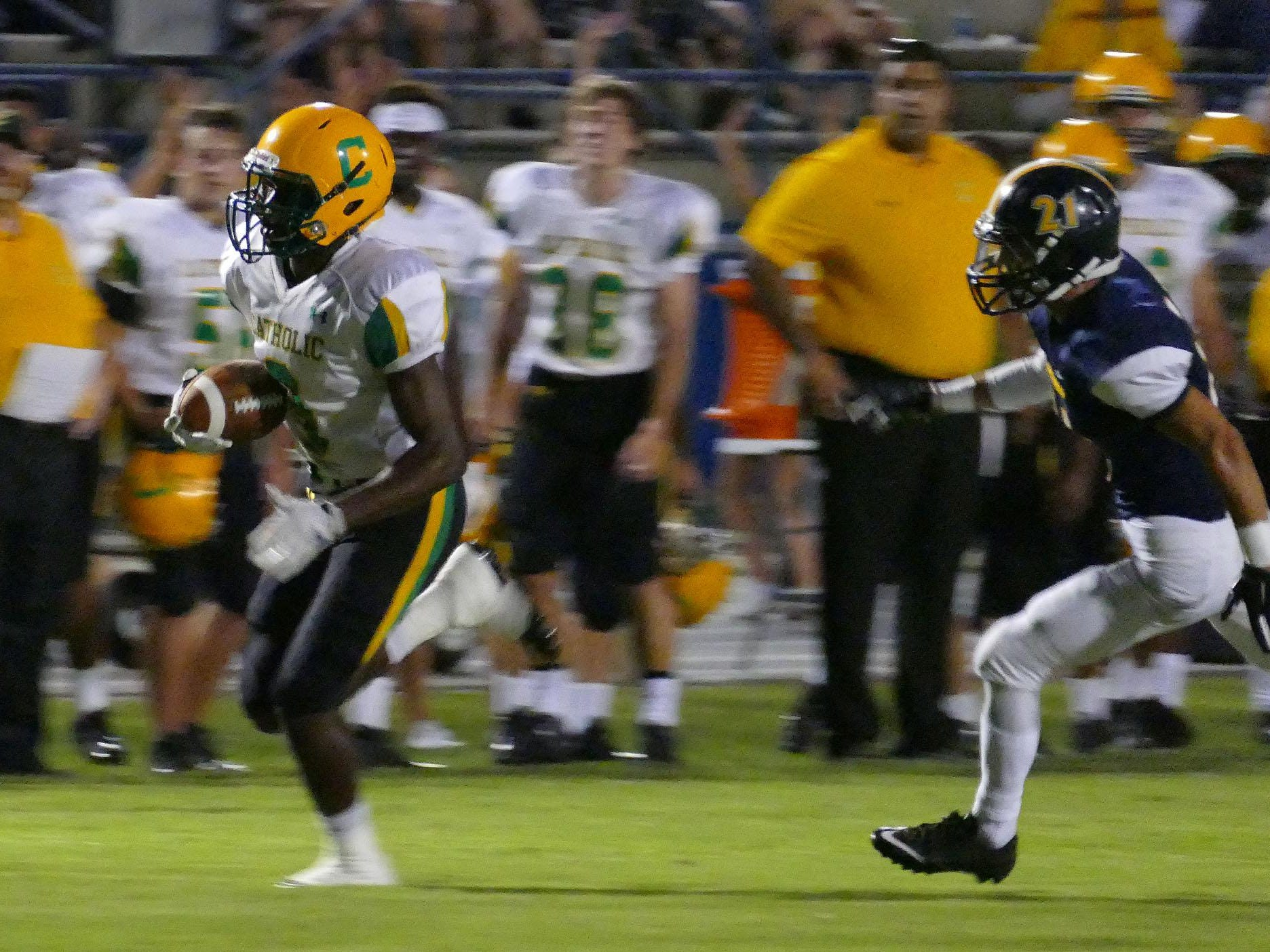 Catholic's Simeon Smiley runs past a Gulf Breeze defender during action this past season. Smiley was named a first-team Class 3A All-State player by the sports writers of Florida.