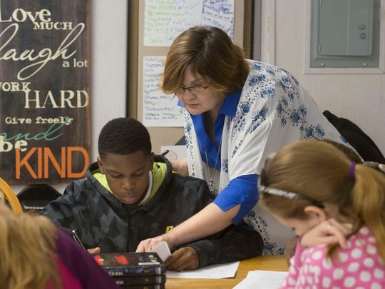 Bellview Middle School seventh-grade English Language Arts teacher, Sheila Miller, helps student, Kylel Grandison, with a writing assignment in preparation for the Florida Standards Assessments.
