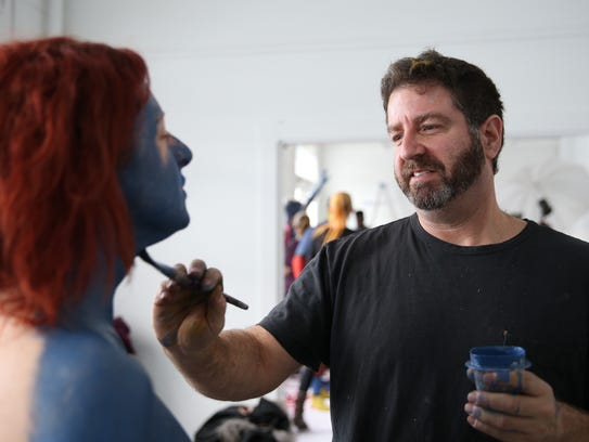 Local artist Andy Golub paints Melanie Fortino during