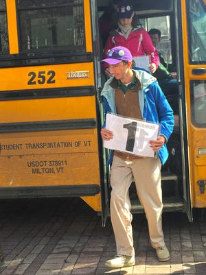 Rice Memorial High School jump off the bus in Burlington on Thursday holding numbers that represent the number of homeless children in Chittenden County.