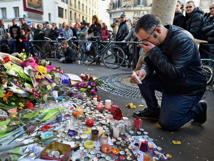 Mourners lay flowers and light candles at La Belle