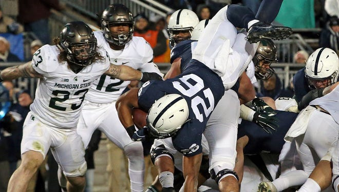Penn State's Saquon Barkley (26) dives over the pile for a touchdown against Michigan State in the first half Nov. 26, 2016.
