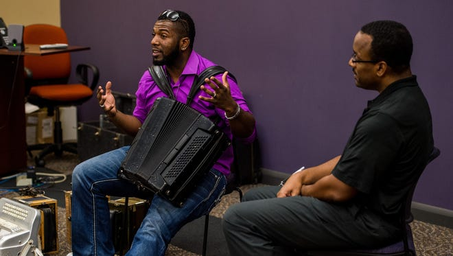 Nathan Williams, Jr. of Lil' Nathan & the Zydeco Big Timers speaks to reporter Herman Fuselier during a performance for the Acadiana Roots series at the Daily Advertiser in Lafayette, La., Thursday, Nov. 12, 2015.