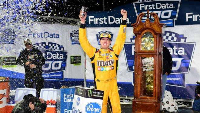 Kyle Busch celebrates next to the winner's grandfather clock after taking the victory at Martinsville Speedway Sunday.