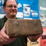 In this photo taken on Thursday, Bay County Historical Museum director Ron Bloomfield holds up a 100-year-old brick that was dug up by Consumers Energy subcontractor on Ninth Street between Washington and Saginaw avenues in Bay City, Mich.