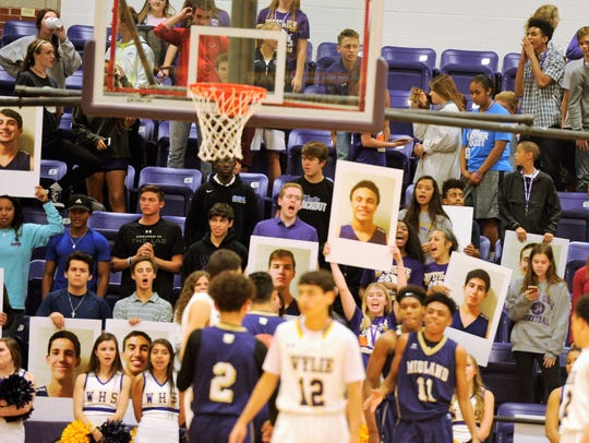 The Wylie student section holds up pictures of the