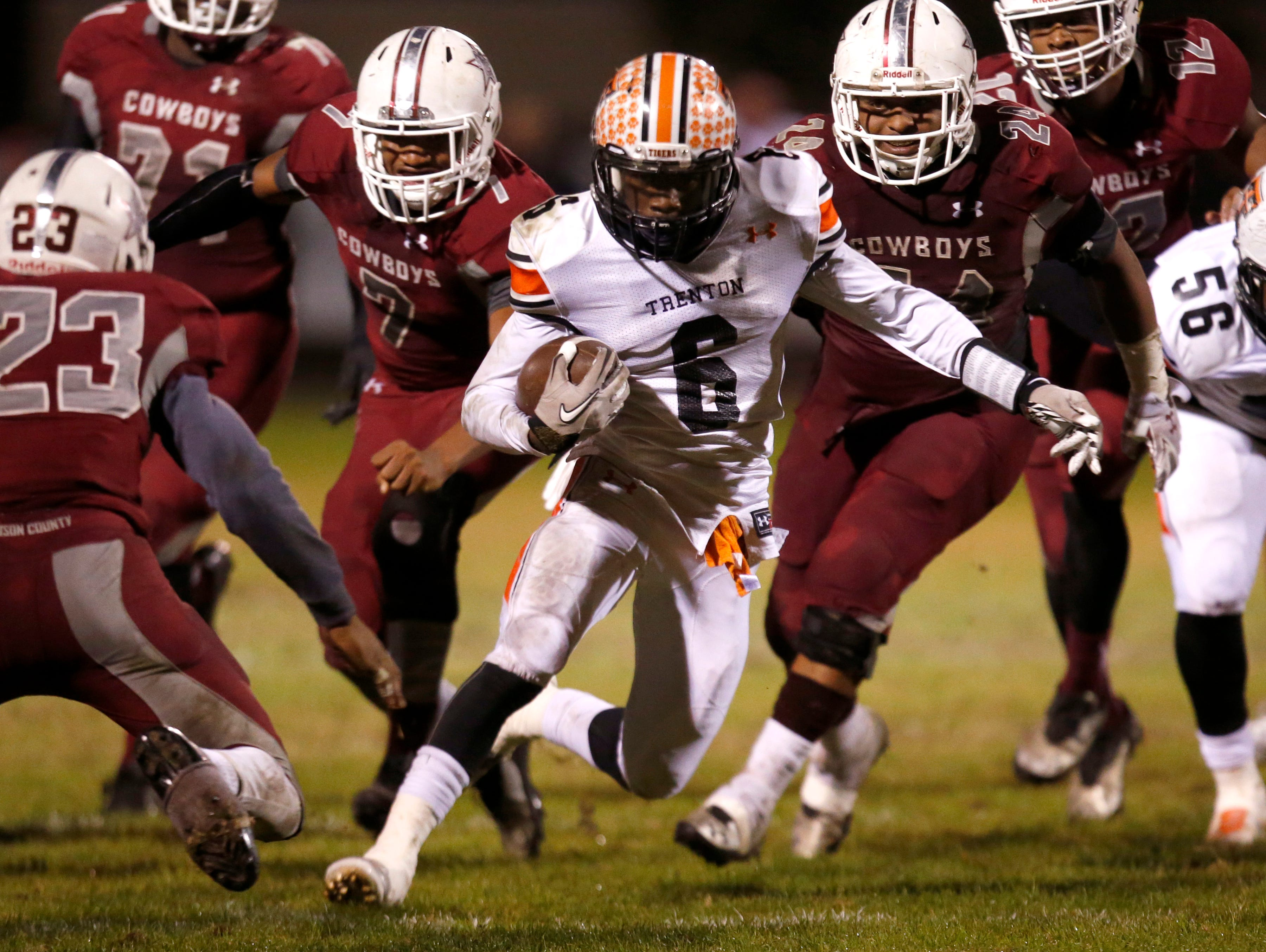 Trenton's Montrez Jackson runs past a host of Madison County defenders during their playoff game on Friday.