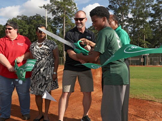 Easias Bass, 13, shares ribbon-cutting duties Tuesday with World Series Champion David Ross at the newly refurbished Capital Park baseball field that received a grant from the Scotts Field Refurbishment Program and Major League Baseball.