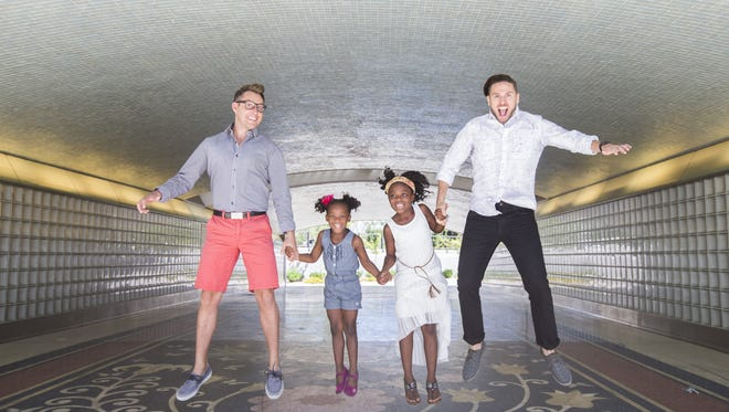Kevin Patterson (L) and David Patterson jump in the underground tunnel with their daughters Cayden (R) and Cayla at Biltmore in Phoenix.