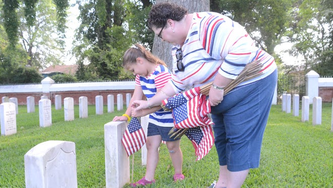 Tracy Tam and daughter Emmalyn Tam place flags on the graves at the Alexandria National Cemetery on Saturday. The Tams and other volunteers put flags on the 7,816 graves. The flags were placed in preparation for Monday's Memorial Day program that will begin at 10 a.m. In case of rain, the program will be moved to the auditorium in Building 8 of the Alexandria VA Medical Center in Pineville.