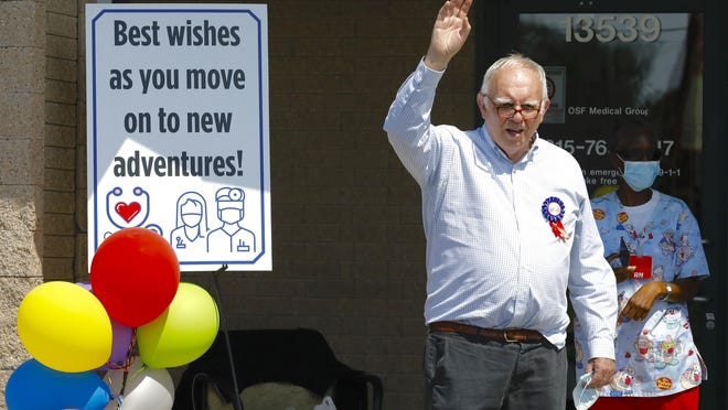 Dr. David Pocock, 74, of Poplar Grove waves to patients, friends and OSF staff as they drive by for his retirement party on Thursday at OSF Medical Group - Primary Care in Poplar Grove.