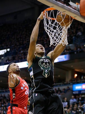 Giannis Antetokounmpo dunks the ball with Raptors guard Norman Powell watching.  Antetokounmpo scored 19 points during the Bucks' 107-77 win.