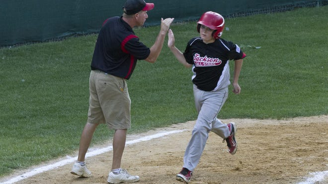 Jackson's Sean Slusak gets a high five from manager Evan Glaser after hitting a two run homer in the second inning. Jackson vs North Wall in Section 3 LL tournament in Manchester, NJ on July 18, 2015.