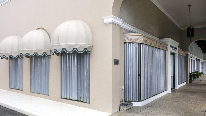 Hurricane shutters were installed on the windows of stores on the south side of Worth Avenue, west of Golfview Road, on Tuesday.