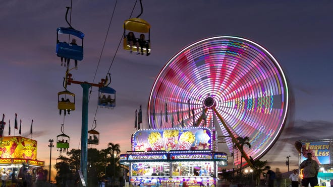 Chair lifts, food, and spinning rides color the night sky as the sun sets on the opening day of the South Florida Fair in January 2019. The annual Palm Beach County fair returns in 2021, from Jan. 17 to Feb. 2.