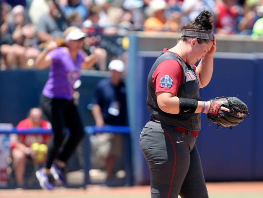 Oklahoma's Paige Parker (8) and Washington coach Heather Tarr (background) react after Parker gave up a home run to Washington in the fifth inning of a Women's College World Series NCAA softball game in Oklahoma City, Sunday, June 3, 2018. (Sarah Phipps/The Oklahoman via AP)