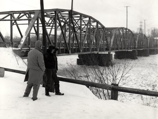 A trio of men overlook the ice-filled Muskingum River