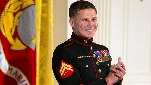 """Retired Marine Cpl. William """"Kyle"""" Carpenter applauds his medical team as they stand to be acknowledged by President Barack Obama during a ceremony presenting Carpenter with the Medal of Honor for conspicuous gallantry, Thursday, June 19, 2014, in the East Room of the White House in Washington. Carpenter received the Medal of Honor for his courageous actions while serving as an Automatic Rifleman in Helmand Province, Afghanistan. (AP Photo/Jacquelyn Martin)"""