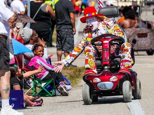 A clown with the Araba Shriners slaps hands with a young girl as he rides by in the 2017 Lehigh Spring Festival Parade.