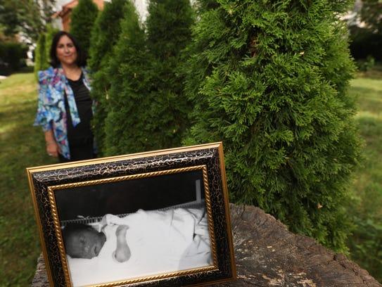 Bereavement counselor Reva Judas stands in her backyard