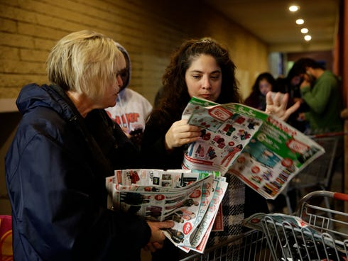 Katie Stroh, left, and Gretchen Burkhardt look at catalogs while waiting outside a Kmart store on Nov. 28 in Anaheim, Calif.