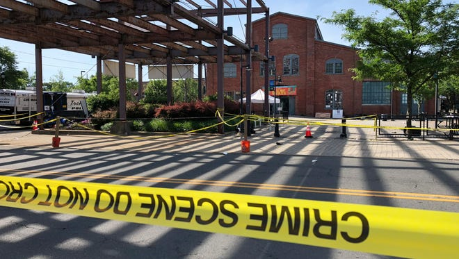 Police crime-scene tape keeps people away from the brick Roebling Wire Works building in Trenton, N.J., hours after a shooting broke out there at an all-night art festival early Sunday.