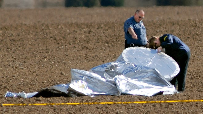 An investigator, right, with the National Transportation Safety Board and an unidentified police officer inspect the scene where a balloon landed Oct. 15, 2009, in a field southeast of Hudson, Colo. The homemade balloon aircraft floated away from a yard in Fort Collins, Colo., after a 6-year-old boy was reported to be seen climbing in, setting off a frantic scramble by the military and law enforcement.