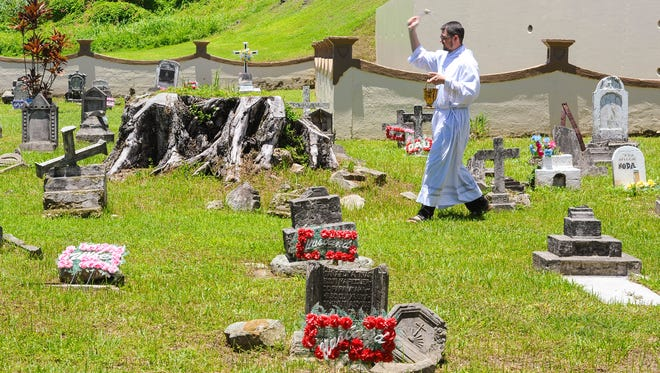 Father Krzysztof Szafarski, of Santa Rita's Our Lady of Guadalupe Church, blesses the graves with holy water at the Sumay Cemetery in the U.S. Naval Base Guam on Wednesday, July 20, 2016. Former Sumay residents, their descendants and others gathered for a memorial Mass, and luncheon that followed immediately after, were coordinated between the base officials and the Santa Rita mayor's office, as part of the island's Liberation Day festivities, according to a Navy release.
