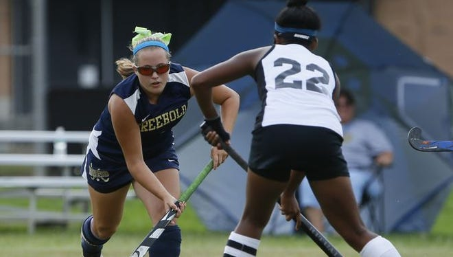 Freehold's Victoria Tiefenthaler and Middletown North's Kaylah Igarta (22) battle for the ball in the Class A North field hockey game on Sep. 20, 2016