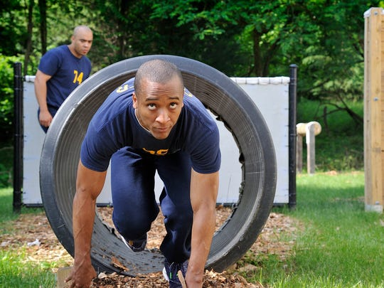 Police cadet Mustafa Lawrence runs the obstacle course