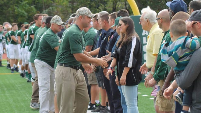St. Joseph football coaches and players greet honorees during last year's Military, Police and Fireman Appreciation Day.