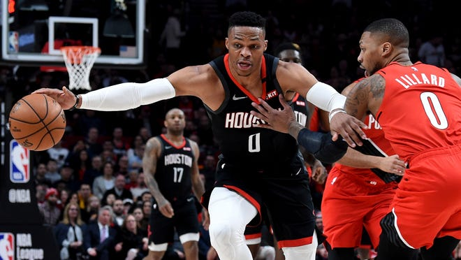 FILE - In this Jan. 29, 2020, file photo, Houston Rockets guard Russell Westbrook, left, dribbles next to Portland Trail Blazers guard Damian Lillard, right, during the first half of an NBA basketball game in Portland, Ore. Westbrook said Monday, July 13, 2020, that he has tested positive for coronavirus, and that he plans to eventually join his team at the restart of the NBA season. Westbrook made the revelation on social media. As recently as Sunday, the Rockets believed that Westbrook and James Harden -- neither of whom traveled with the team to Walt Disney World near Orlando last week -- would be with the team in the next few days. In Westbrook's case, that now seems most unlikely.
