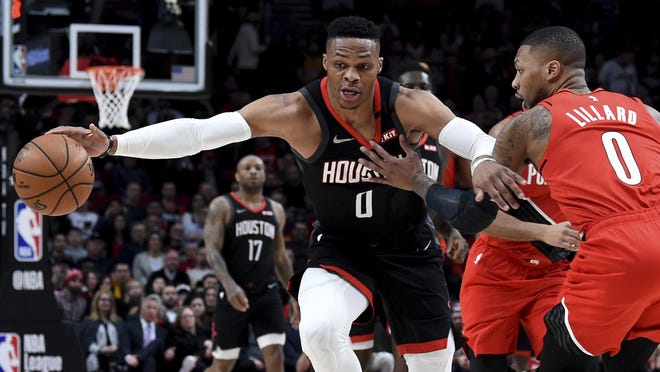 """FILE - In this Jan. 29, 2020, file photo, Houston Rockets guard Russell Westbrook, left, dribbles next to Portland Trail Blazers guard Damian Lillard, right, during the first half of an NBA basketball game in Portland, Ore. Westbrook said Monday, July 13, 2020, that he has tested positive for coronavirus, and that he plans to eventually join his team at the restart of the NBA season. Westbrook made the revelation on social media. As recently as Sunday, the Rockets believed that Westbrook and James Harden â€"""" neither of whom traveled with the team to Walt Disney World near Orlando last week â€"""" would be with the team in the next few days. In Westbrook's case, that now seems most unlikely."""