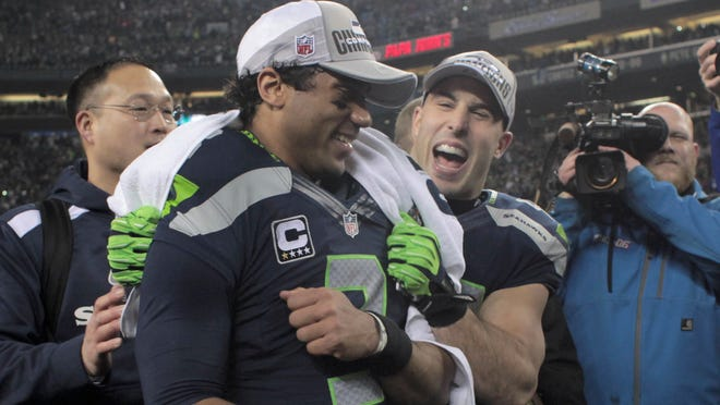 Seattle Seahawks quarterback Russell Wilson (L) celebrates with teammate Chris Maragos after defeating the San Francisco 49ers in the NFL's NFC Championship football game in Seattle, January 19, 2014. REUTERS/David Ryder (UNITED STATES  - Tags: SPORT FOOTBALL)   ORG XMIT: SEA13