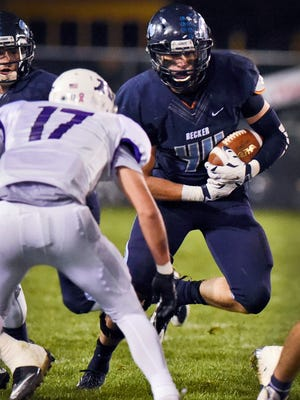 Becker's Beau Pauly (right, 44) runs the ball against Albany during the first half Oct. 8 in Becker.