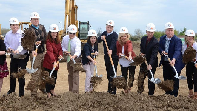 South Lyon Schools board members and administrators join with former Superintendent William A. Pearson, center, in blue, at the ground-breaking ceremony Saturday for the district's newest elementary school: William A. Pearson Elementary School.