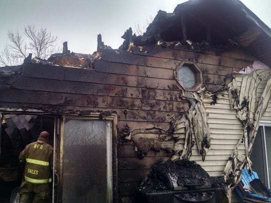 A Brooklyn firefighter examines the damage at 5231 Skyline Drive, Holiday Lake, after a fire destroyed the residence.