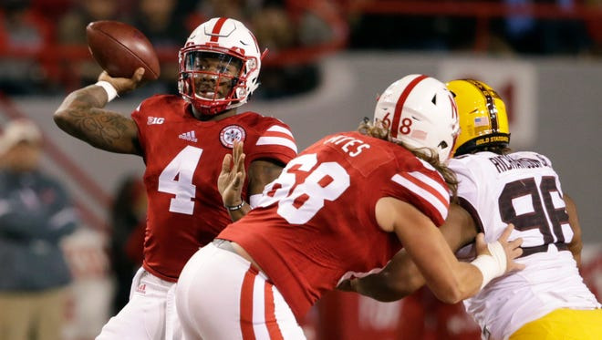 Nebraska quarterback Tommy Armstrong Jr. (4) throws as offensive lineman Nick Gates (68) blocks Minnesota defensive lineman Steven Richardson (96) during the first half of an NCAA college football game in Lincoln, Neb., Saturday, Nov. 12, 2016.