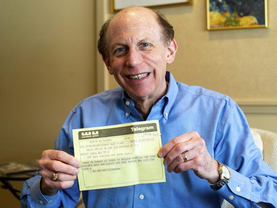 Robert Fink holds up a telegram from a family friend congratulating him on his 1969 graduation from the University of Michigan at his home in Huntington Woods on Friday, March 1. The telegram, delivered to his apartment the day after he moved away from Ann Arbor, was recovered 50 years later by an employee of a downtown Ann Arbor company in a filing cabinet bought from the University of Michigan