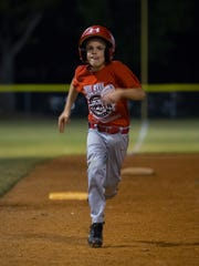 Chris Patrick Jr., 9, runs to home plate to score during