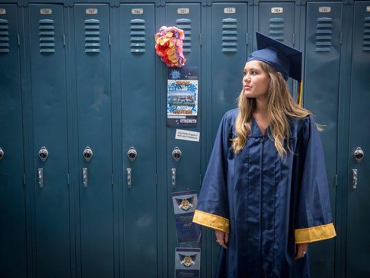 Delta High School graduate Olivia Shoemaker stands