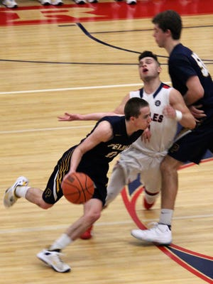 Pelham's Ryan O'Neil drives around Eastchester's Benny DiMirco during Pelham's 64-60 win in a Class A first-round playoff game at Eastchester High School on Feb. 16, 2016.